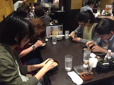 自主ゼミ後のお食事会も楽しみの一つ。とんかつ屋でゴマをする人々笑